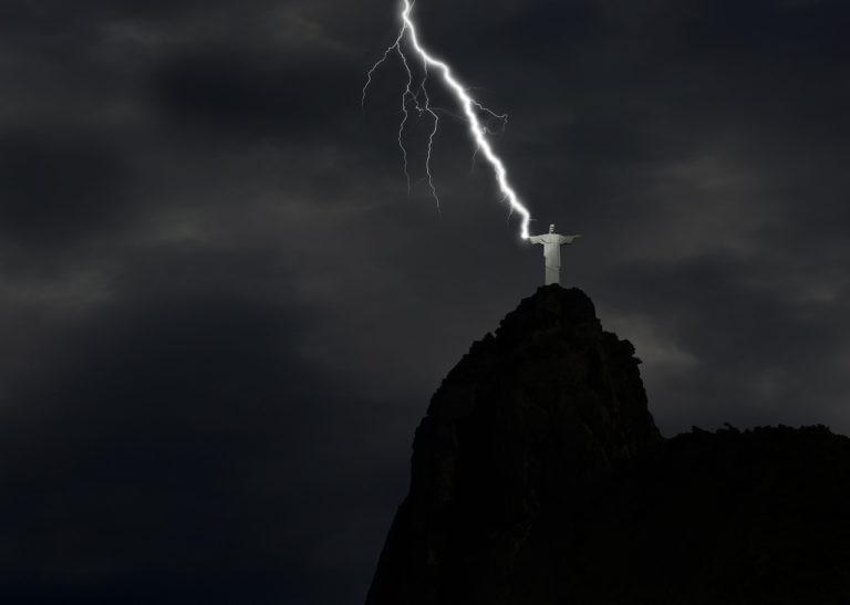 An image of a man in white robes on top of a hill with his arms spread wide. A bolt of lightning is striking his right hand.
